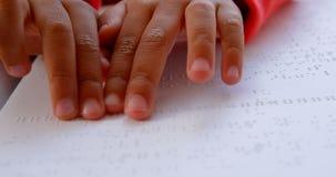 W g?r? niewidomej Azjatyckiej uczniowskiej r?ki czyta Braille ksi??k? w sali lekcyjnej przy szko?? 4k zbiory wideo