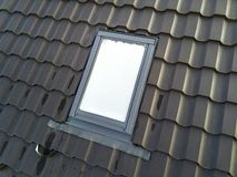 W g?r? nowego strychowego plastikowego okno instaluj?cego w shingled domu dachu Profesjonalnie robi? budynek i robot budowlany, d obrazy royalty free