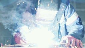 W g?r?, spawacz spawa dwa metal cz??ci Robociarz w coveralls pracuje indoors, zwolnione tempo zbiory wideo