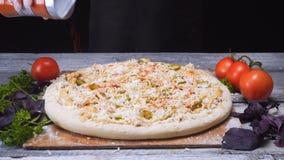 W g?r? szef kuchni r?k w krzem r?kawiczkach dodaje pikantno?? na g?rze pizzy na drewnianym stole Rama pyszna pizza obrazy royalty free