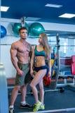 W gym Wizerunek ładni dziewczyn spojrzenia przy bodybuilder Obraz Royalty Free