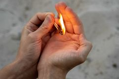 W jego rękach płonący matchs i piaska tło obraz stock