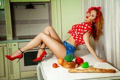 W kuchennej gospodyni domowej pozuje na stole w pinup stylu Zdjęcia Royalty Free