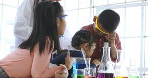 W laboranckim pokoju, chłopiec spojrzenie przez mikroskopu zbiory