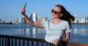 W lecie dziewczyna na tle duży miasto i nabrzeże bierzemy selfie na smartphone zbiory