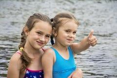 W lecie na rzece, dwa małej siostry w kostiumach kąpielowych a zdjęcie stock