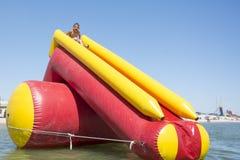 W lecie, na słonecznym dniu przy morzem chłopiec rusza się out na inflat Obrazy Royalty Free