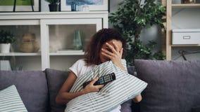 W młodej damy amerykanin afrykańskiego pochodzenia dziewczyny dopatrywania horrorze na TV i chować za poduszki obsiadaniem na leż zbiory
