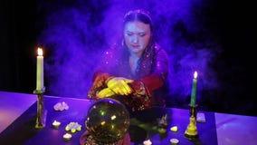 W magicznym salonie gypsy czyta przyszłość w magicznej piłce otaczającej świeceniem i dymem zbiory