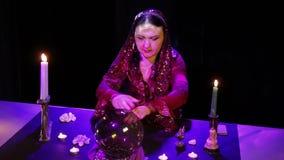 W magicznym salonie gypsy czyta przyszłość w magicznej piłce otaczającej świeceniem zbiory