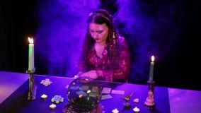 W magicznym salonie gypsy rozkłada karty na stole w chuchu dym zbiory