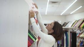 W modnym, lekkim tkanina sklepie wśród różnorodność tkanin szczęśliwa żeńska nabywca bierze out lekką tkaninę od zbiory wideo
