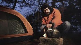 W noc lesie, turysta blisko namiotu zaczynał ogienia, i czajnik ustawiał nad ogień Mężczyzna usuwa zbiory wideo