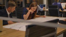 W nowożytnym biura trzy personelu przy stołowym spojrzeniem rozmowa i papier Rzuca gllass widok zbiory