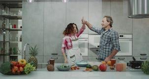 W nowożytnej kuchni dojrzałej parze wydaje romantycznego czas wpólnie podczas gdy gotujący jedzenie one dacing bardzo charyzmatyc zbiory