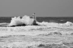Włochy, ` Mangiabarche `, burza Fala roztrzaskanie przeciw latarni morskiej lub bakanowi Zdjęcie Stock
