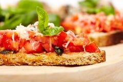 Włoscy pomidorowi bruschettas dekorowali z basilem i parmesan Fotografia Royalty Free