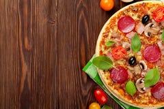 Włoska pizza z pepperoni, pomidorami, oliwkami i basilem, Obrazy Stock