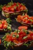 W?oski pomidorowy bruschetta z warzywami, ziele i olejem na skorupiastym ciabatta chlebie siekaj?cymi, piec na grillu lub wznosz? obraz stock