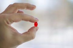W palcach trzyma czerwoną pigułkę tło zamazujący światło Obrazy Royalty Free