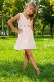 W parku mała dziewczynka uśmiechnięci stojaki zdjęcia stock
