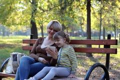 W parku matki i córki obsiadanie Zdjęcia Royalty Free