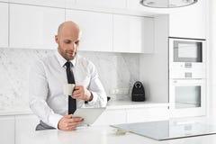 W połowie dorosły biznesmen ma kawę podczas gdy używać pastylka peceta przy kuchennym kontuarem Fotografia Royalty Free