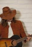 W połowie dorosły mężczyzna jest ubranym kowbojskiego kapelusz i bawić się gitarę Zdjęcie Stock