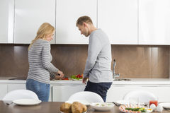 W połowie dorosły pary narządzania posiłek wpólnie w kuchni fotografia royalty free