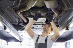 W połowie dorosły samochodu mechanika naprawiania samochód w warsztacie obrazy royalty free