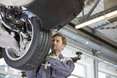 W połowie dorosły technika naprawiania samochód toczy wewnątrz warsztat zdjęcie stock