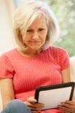 W połowie pełnoletnia kobieta używa pastylkę w domu zdjęcia royalty free