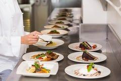 W połowie sekcja żeński szefa kuchni garnirowania jedzenie w kuchni fotografia royalty free