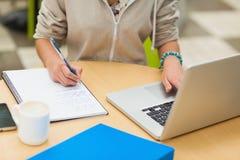 W połowie sekcja żeński uczeń robi pracie domowej laptopem zdjęcie royalty free