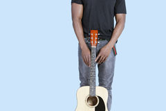 W połowie sekcja amerykanina afrykańskiego pochodzenia mężczyzna z gitarą nad bławym tłem Zdjęcia Royalty Free