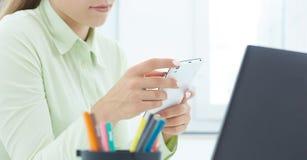 W połowie sekcja beautifulyoung dziewczyny mienia telefonu komórkowego obsiadanie przy biurem Biznes, wekslowy rynek, oferta prac zdjęcia stock