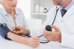 W połowie sekcja bierze ciśnienie krwi jego pacjent lekarka fotografia stock