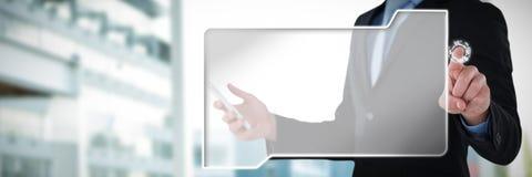 W połowie sekcja biznesmena mienia telefon komórkowy podczas gdy używać interfejsu ekran przeciw pracującemu biurku wewnątrz zdjęcie royalty free