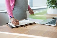 W połowie sekcja ciężarny bizneswomanu writing w organizatorze przy biurkiem Obraz Royalty Free
