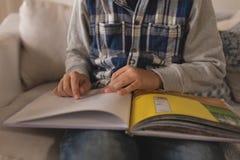 W połowie sekcja czyta opowieści książkę w żywym pokoju chłopiec obraz royalty free