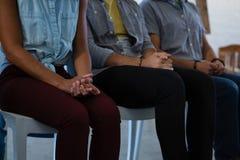 W połowie sekcja dorosli ucznie z rękami spinał obsiadanie na krześle zdjęcie royalty free