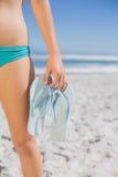 W połowie sekcja dysponowana kobieta w bikini na plażowych mienia trzepnięcia klapach zdjęcie stock