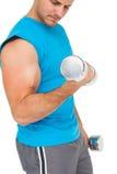 W połowie sekcja dysponowany młody człowiek ćwiczy z dumbbells zdjęcie royalty free