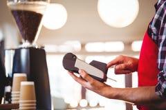 W połowie sekcja kelner używa kredytową karcianą maszynę fotografia royalty free