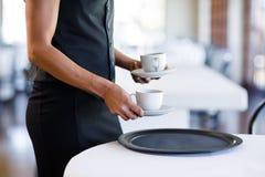 W połowie sekcja kelnerki słuzyć filiżanka kawy fotografia stock