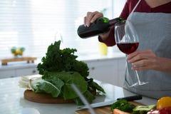 W połowie sekcja kobieta ma czerwone wino przy stołem obraz stock