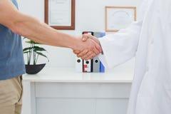 W połowie sekcja lekarka i pacjenta chwiania ręki obraz royalty free