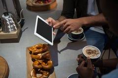 W połowie sekcja mężczyzna używa cyfrową pastylkę podczas gdy mieć kawę fotografia royalty free