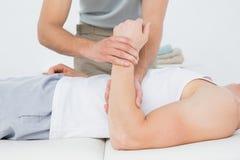 W połowie sekcja męska lekarka egzamininuje pacjent rękę Obraz Stock