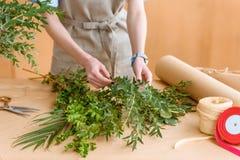 w połowie sekcja młoda kwiaciarnia w fartuchu układa zielone rośliny obraz royalty free